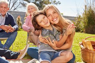 Mutter umarmt ihren Sohn bei einem Picknick