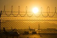 security fence around international airport at sunrise