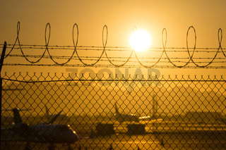 security fence around international airport at sunrise