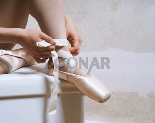 unrecognizable ballerina tying her pointe or ballet shoes