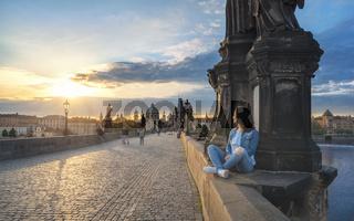 Girl watching the sunrise on Charles Bridge
