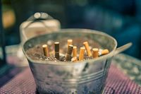 Cigarette butts in a tin bowl in front of a restaurant