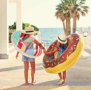 Two small girls with inflatable toys on the beach