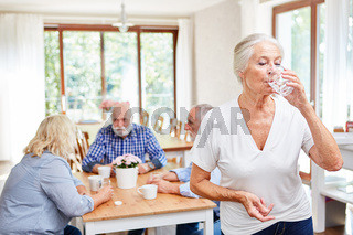 Seniorin nimmt eine Tablette als Medizin