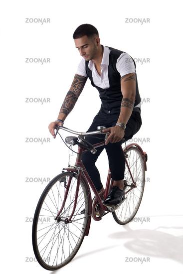 Tattoed elegant man riding his bicycle in istudio