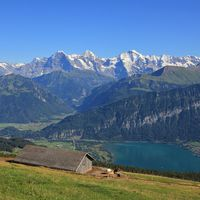 Snow capped mountains Eiger, Monch and Jungfrau, view from Mount Niederhorn. Azure blue Lake Thun, B