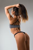Fitness model wearing black tanga cropped rearview