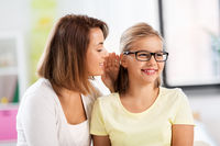 happy mother whispering secret to daughter at home