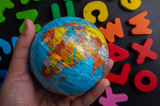 Hand holding a globe model on colorful letters on a black background