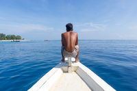 Local Sporty Guy Sitting Topless at the Bow of Traditional White Wooden Sail Boat, Looking At Beautiful Blue Sea of Gili Islands near Bali, Indonesia