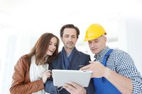 Worker and couple look at tablet