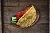 Top view of plain egg omelette with tomato and cucumber on rustic wooden background