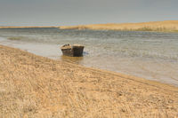 The boat in the water. Rowing boats in the reeds. Wooden boat on the lake on a summer day. Aral sea,
