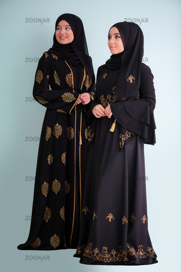 two hijab muslim woman on cyan background