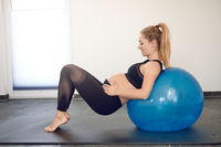 Pregnant woman working out with a pilates ball