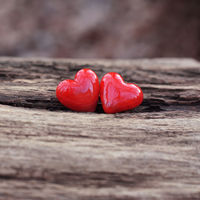two red ceramic hearts on wooden background with copy space