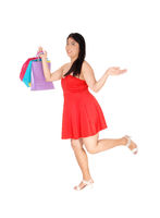 Happy Chinese woman running with her shopping bags