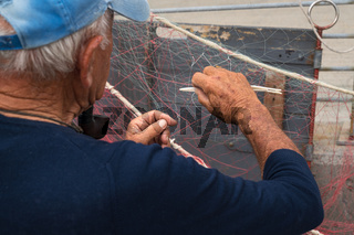 Senior fisherman is fixing a fishing net