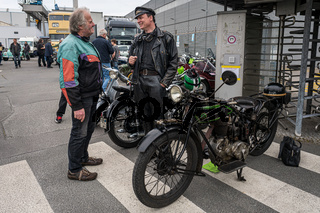 The owner of a motorcycle D-Rad R-O / 4, dressed in the style of the 20s, talking to a visitor.