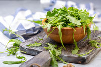 Arugula leaves for salad in a wooden bowl.