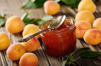 Glass Jar of Apricot jam on wooden table with ripe apricots at background