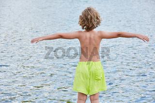 Kleiner Junge in Shorts steht am Ufer am Meer