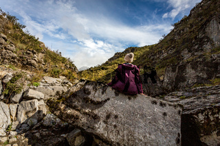 Woman sitting on rock with sea fossils more than 1200 mtrs above sea