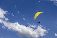 Oostduinkerke, Belgium - June 19, 2019: A paraglider is floatring in the air between wihte clouds