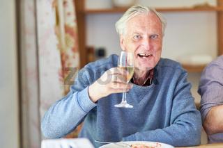 Vergnügter Senior mit Sektglas beim zuprosten