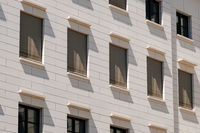 windows building facade with closed shutters / sun blinds