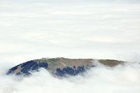 Bergrücken lugt durch die Wolkendecke