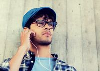 man with earphones listening to music on street