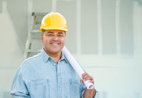 Hispanic Male Contractor with Blueprint Plans Wearing Hard Hat In Front of Drywall and Ladder