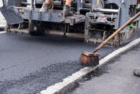 Asphalting a road - road paver with broom