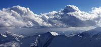 Panoramic view on snowy sunlit mountains