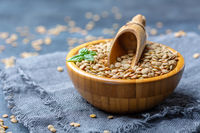 Brown organic dried lentils in a wooden bowl.