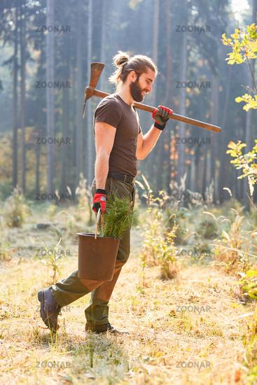 Waldarbeiter mit Setzling und Wiedekopfhaue