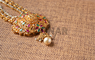 Gold Guttapusalu Necklace with gemstones a traditional Indian wedding jewelry on wooden textured background.