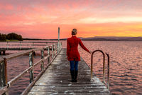 Woman on rustic timber jetty watching beautiful sunset