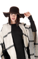 Lovely woman standing in black dress with a poncho and hat