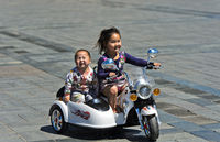 Girl riding an electric toy motor-bike with her brother on Sukhbaatar Square,Mongolia