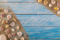 Summer time concept with sea shells on a blue wooden background and sand