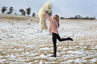 Woman frolicking in the snow with teddy bear