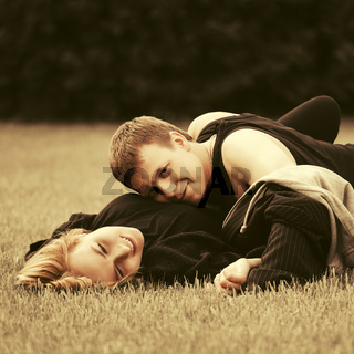 Happy young couple in love lying on grass in city park
