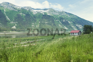Scenic Landscape With Grass Field, Old Wooden House, River And High Mountain Near Haines, Alaska