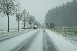 snow storm on a country road and dangerous road conditions in winter with cars driving