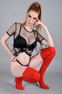 Sexy, schlanker, vollbusige Rothaarige, der ein reines Oberteil tragt und rote Stiefel