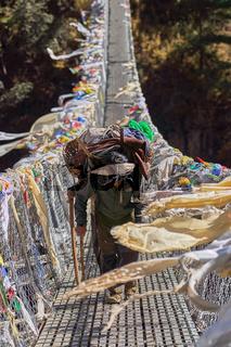 Träger auf einer Hängebrücke in Nepal