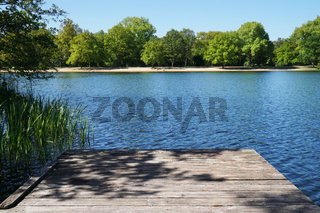 empty wooden pier or jetty overlooking lake