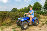 Young man driving quad in nature